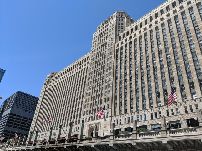 The Merchandise Mart (or the Merch Mart, or the Mart) is a commercial building located in downtown Chicago, Illinois. When it was opened in 1930, it was the largest building in the world, with 4,000,000 square feet (372,000 m2) of floor space.[1][2] The art deco structure is located at the junction of the Chicago River's branches. The building is a leading retailing and wholesale destination, hosting 20,000 visitors and tenants per day as of the late 2000s.[3][4]  Built by Marshall Field & Co. and later owned for over half a century by the Kennedy family, the Mart centralized Chicago's wholesale goods business by consolidating architectural and interior design vendors and trades under a single roof.[2] It has since become home to several other enterprises, including the Shops at the Mart, the Chicago campus of the Illinois Institute of Art, Motorola Mobility, and the Chicago tech startup center 1871